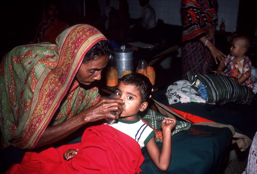Grandmother caring for boy in Dhaka infectious diseases ward Bangladesh