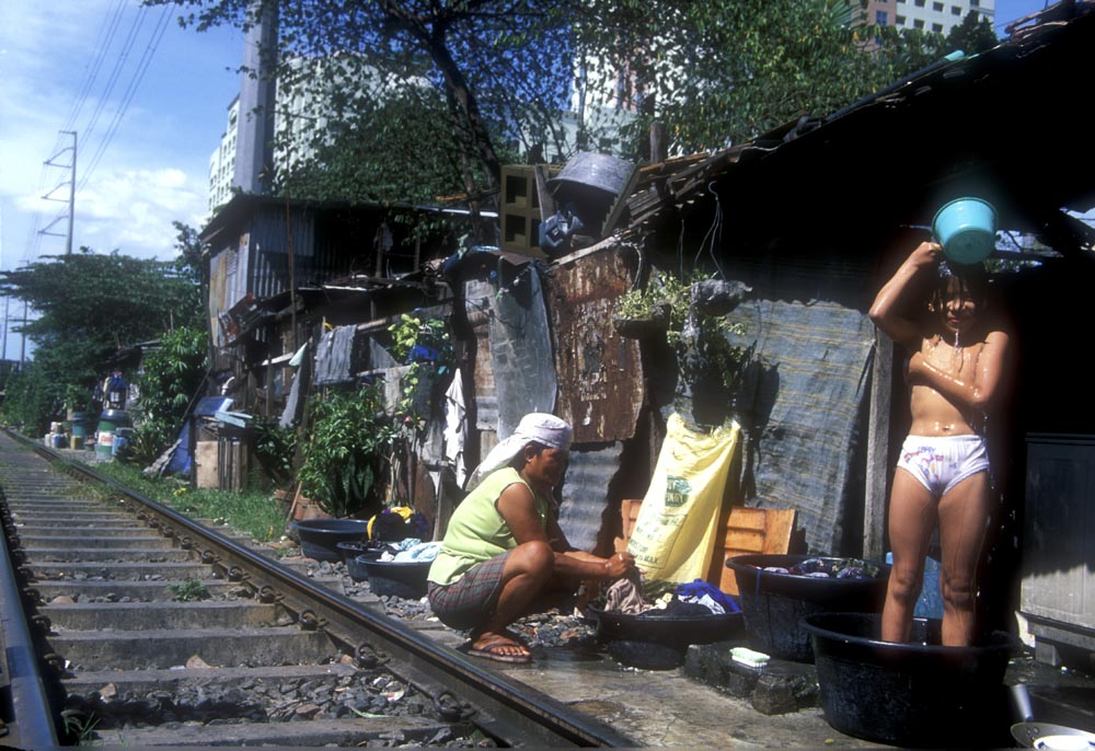 Railway life with child washing in a tub Manila Philippines