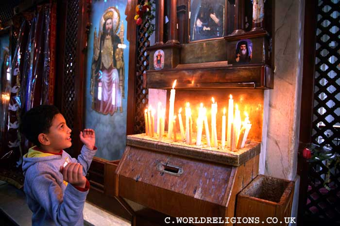 Coptic Christian boy  prays in the Church of the Holy Virgin in Cairo Egypt