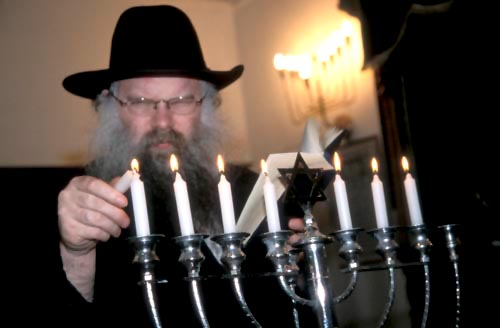 Rabbi lights chanukkah candles left to right