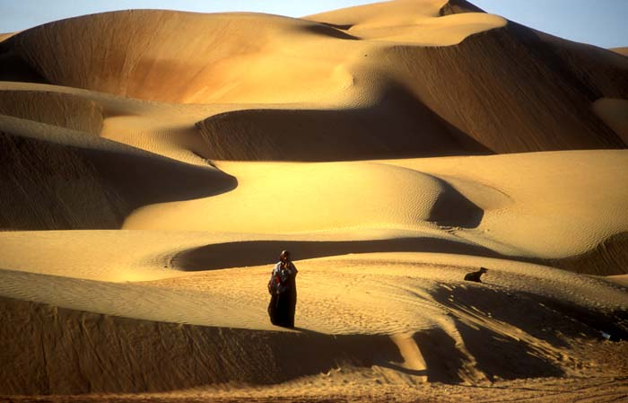 HUge sand dunes in the Sharqiya Province of Oman with a Bedouin woman searching for a stray goat